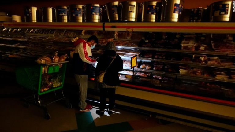 Customers at a grocery store in Dallas on Tuesday use the light from a cell phone to look in the meat section. Though the store lost power, it was open for cash only sales.