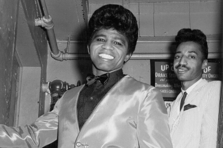 NEW YORK - 1964: 'Godfather of Soul' James Brown backstage at the Apollo Theatre with his cape man Danny Ray in 1964 in New York, New York. (Photo by Don Paulsen/Michael Ochs Archives/Getty Images)