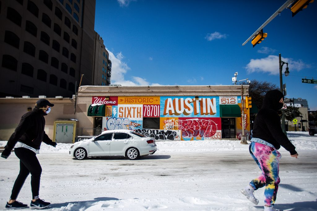 AUSTIN, TX - FEBRUARY 15: Pedestrians walk on along a snow-covered street on February 15, 2021 in Austin, Texas. Winter storm Uri has brought historic cold weather to Texas, causing traffic delays and power outages, and storms have swept across 26 states with a mix of freezing temperatures and precipitation. (Photo by Montinique Monroe/Getty Images)