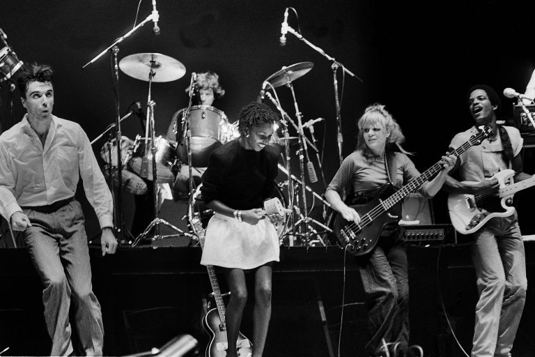 American New Wave group Talking Heads perform onstage at the Poplar Creek Music Theater, Hoffman Estates, Illinois, August 16, 1982. Pictured are, from left, David Byrne, Chris Frantz (on drums), Dolette McDonald, Tina Weymouth (on bass), and Alex Weir (on guitar). (Photo by Paul Natkin/Getty Images)