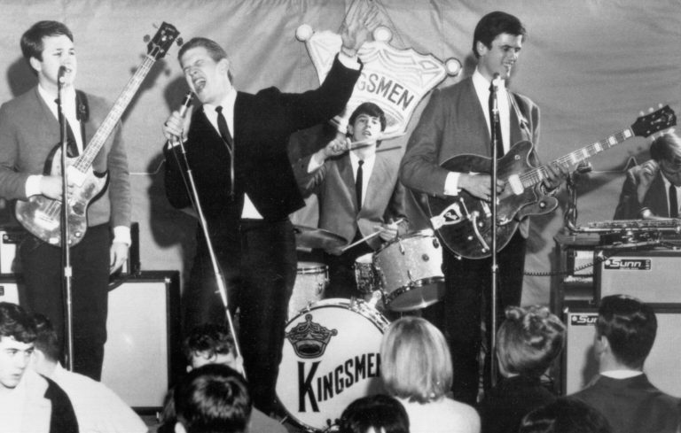 "CIRCA 1964:  (L-R) Norm Sundholm, Lynn Easton, Dick Peterson, Mike Mitchell, and Barry Curtis of the touring version of the rock and roll band ""The Kingsmen"" perform onstage in 1964. (Photo by Michael Ochs Archives/Getty Images)"