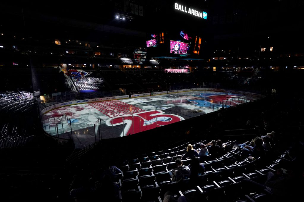 A spotlight hits fans, who were allowed into Ball Arena for the first time since last year because of the coronavirus, as they wait for the start of the first period of an NHL hockey game between the Arizona Coyotes and Colorado Avalanche Wednesday, March 31, 2021, in Denver. (AP Photo/David Zalubowski)