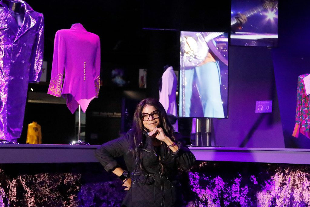 Musician Prince's sister Tyka Nelson poses for photographers in front of 'Purple Rain'  era costumes at the 'My Name is Prince' exhibition at the O2 Arena in London, Thursday, Oct. 26, 2017. The exhibition showcases hundreds of never before seen artefacts direct from Paisley Park, Prince's famous Minnesota private estate. Visitors will get a unique insight into the life, creativity and vision of one of the most naturally gifted recording artists of all time from October 27, 2017 until January 7, 2018.(AP Photo/Frank Augstein)