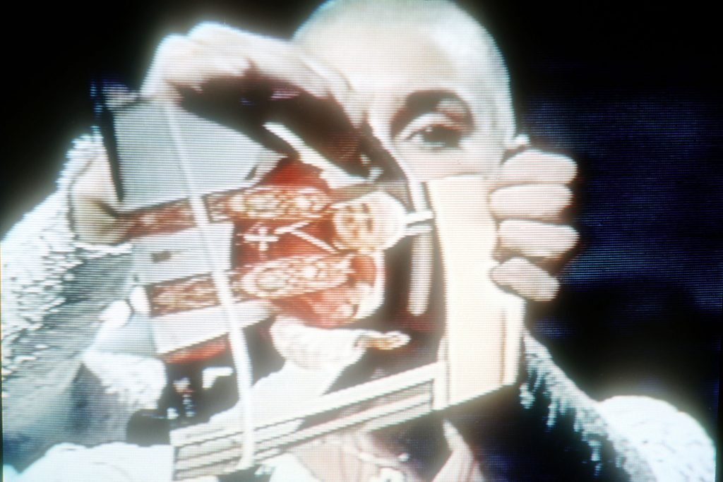 """NEW YORK - OCTOBER 3: (VIDEO CAPTURE) Singer Sinead  O'Connor rips up a picture of Pope John Paul II October 3, 1992 on the TV show """"Saturday Night Live"""". (Photo by Yvonne Hemsey/Getty Images)"""