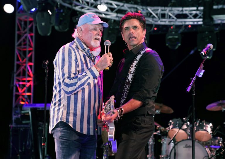Mike Love, left, of The Beach Boys, performs with guest member John Stamos during the Concerts In Your Car series at the Ventura County Fairgrounds, Friday, Oct. 23, 2020, in Ventura, Calif. (AP Photo/Chris Pizzello)